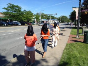 The silent protest involved about 20 people. These few walk down Monroe Avenue in Brighton at 12 Corners. / Gary McLendon/staff photographer